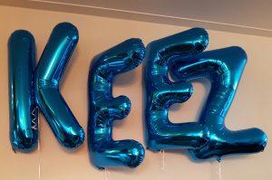 Blauwe grote folie letters met helium gevuld op hoogte zwevend op kraamfeest.